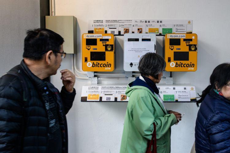 Sejumlah orang melintasi mesin ATM bitcoin di Hongkong. Gambar diambil pada 18 Desember 2017.
