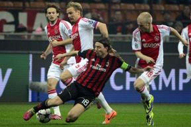 Gelandang AC Milan, Ricardo Montolivo, saat berebut bola dengan para pemain Ajax Amsterdam pada matchday keenam Grup H Liga Champions di Stadion San Siro, Rabu atau Kamis (12/12/2013) dini hari WIB.