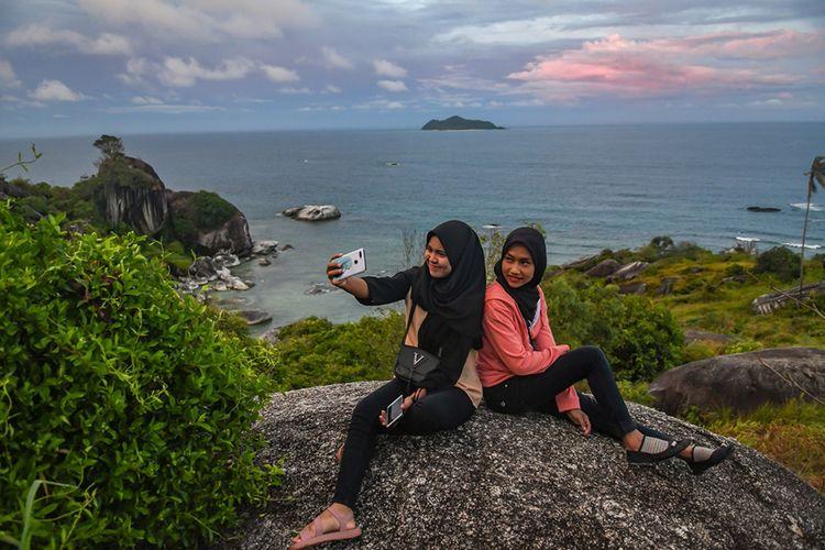 Wisatawan berfoto di lokasi wisata Batu Sindu di kawasan Tanjung Senubing, Bunguran Timur, Natuna, Kepulauan Riau, Minggu (16/2/2020). Tempat wisata ini menawarkan pemandangan batuan yang membentuk morfologi unik dan dikenal sebagai tor granit.