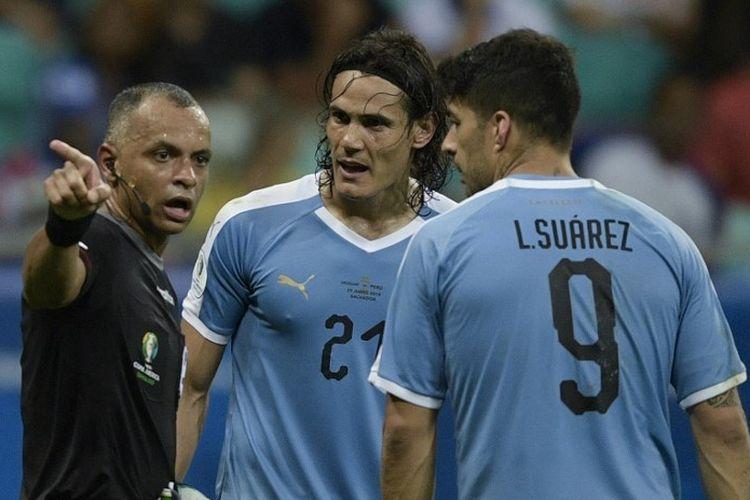 Wasit Wilton Pereira Sampaio berbicara dengan Edinson Cavani dan Luis Suarez pada pertandingan Uruguay vs Peru dalam babak perempat final Copa America 2019 di Fonte Nova Arenam 29 Juni 2019.