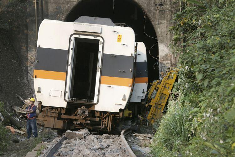 Seorang pekerja pada Sabtu (3/4/2021) berdiri di belakang gerbong kereta Taiwan yang anjlok di kota Hualien. Kecelakaan kereta Taiwan terjadi akibat gerbong anjlok setelah bertabrakan dengan kendaraan yang turun mundur tanpa pengemudi dari atas bukit. Insiden ini menewaskan setidaknya 50 orang.