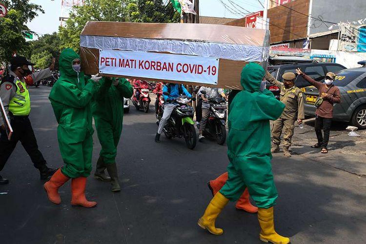 Petugas dari Kelurahan Pondok Labu membawa peti mati saat sosialisasi mencuci tangan, menjaga jarak, menggunakan masker di kawasan RW 05 dan Pasar Pondok Labu, Jakarta Selatan, Rabu (9/9/2020). Sosialisasi terkait bahaya penularan Covid-19 ini dihadiri Camat Cilandak.