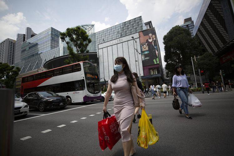 Orang-orang berjalan memakai masker di Orchard Road, Singapura (12/3/2020), sebagai tindakan pencegahan agar tidak tertular virus corona.