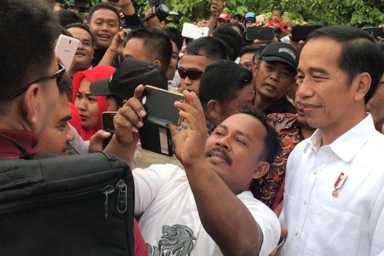 Presiden Joko Widodo saat diminta swafoto bersama salah satu warga di Kabupaten Dharmasraya, Sumatera Barat.