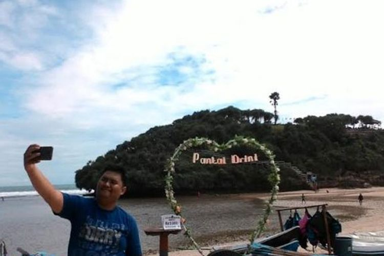 Wisatawan tengah berswafoto di Pantai Drini, Gunungkidul, DI Yogyakarta, Selasa (28/3/2017).