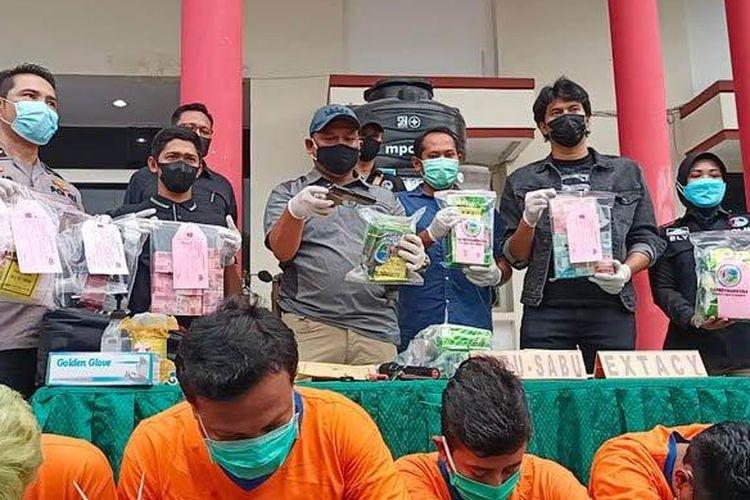 SURYA.CO.ID/Sugiharto Anggota Satnarkoba Polrestabes Surabaya menunjukkan barang bukti berupa sabu-sabu seberat 8,5 Kg, senjata api, mobil dan uang ratusan juta rupiah di Mapolrestabes Surabaya, Selasa (9/3/2021).