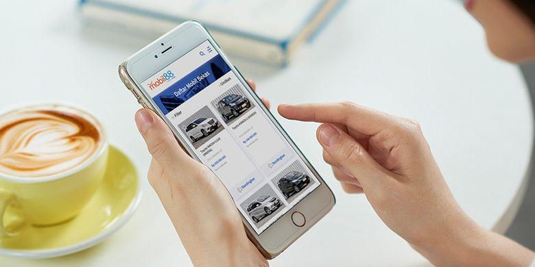 Ilustrasi mencari mobil bekas dari gawai di tangan.