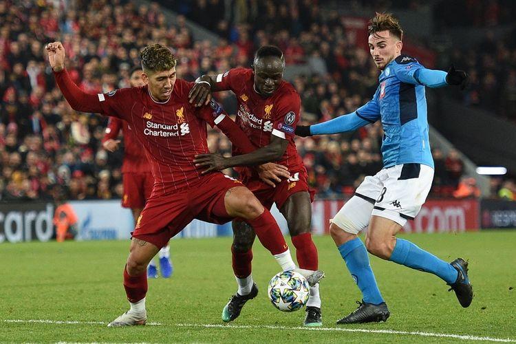 Penyerang Liverpool Roberto Firmino (kiri) bersaing dengan bek Napoli Fabian Ruiz dalam pertandingan sepak bola Liga Champions antara Liverpool vs Napoli di Anfield di Liverpool, pada 27 November 2019.