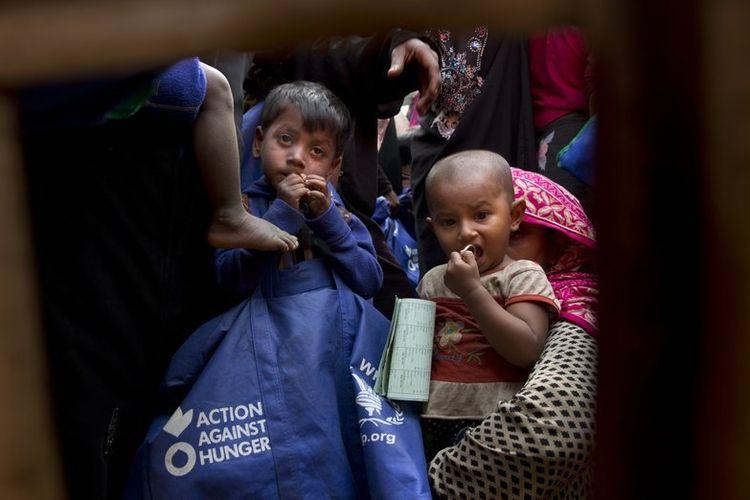 Anak-anak etnis Rohingya dan ibu mereka menunggu giliran untuk menerima paket makanan dari Program Pangan Dunia di kamp pengungsi Balukhali dekat Coxs Bazar, Bangladesh. Foto diambil pada 15 Januari 2018. (AP Photo)