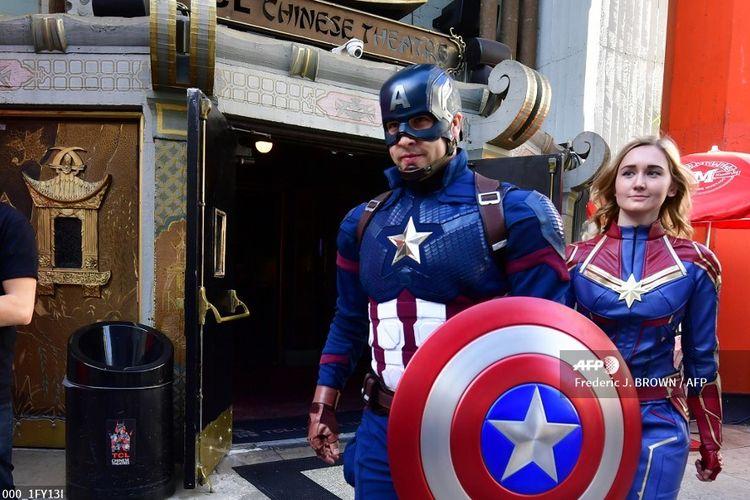 Dua penggemar mengenakan kostum Captain America dan Captain Marvel saat mengikuti lomba kostum menjelang pemutaran Avengers: Endgame di TCL Chinese Theater, Hollywood, California, Kamis (25/4/2019).