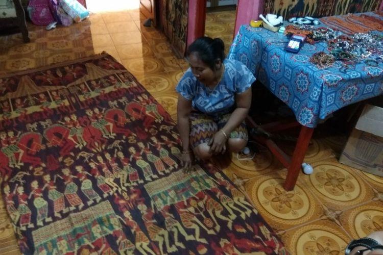 Seorang ibu menunjuk kain tenun khas Sumba.