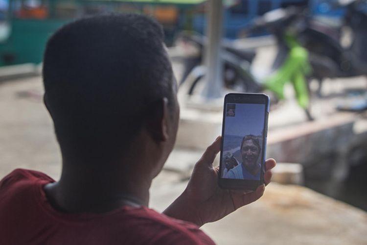 Heriman (42), seorang pengepul ikan tangkapan nelayan mengakses internet menggunakan gawai  di Teluk Baruk, Sepempang, Natuna, Selasa, 8 Oktober 2019.