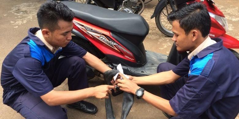 Dua siswa SMK N 1 Kedungwuni, Pekalongan, Jawa Tengah, mempraktekkan cara kerja tambal ban portabel yang menjadi temuannya.