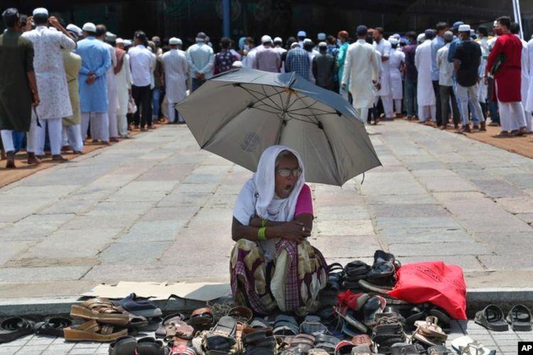 Seorang perempuan duduk di bawah naungan payung dan mengawasi alas kaki para jemaah yang datang untuk shalat Jumat terakhir di bulan suci Ramadan, di Masjid Mekkah, Hyderabad, India, Jumat, 7 Mei 2021.