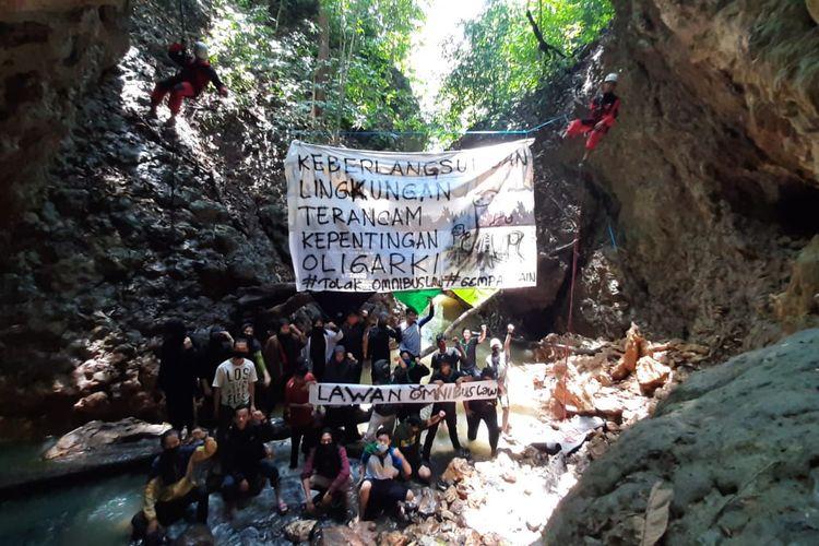 Mahasiswa Pencinta Alam dari Institute Agama Islam Negeri (IAIN) Samarinda membentang spanduk penolakan omnibus law UU Cipta Kerja di batuan karst tebing air terjun, Berambai, Samarinda, Kaltim, Minggu (25/10/2020).