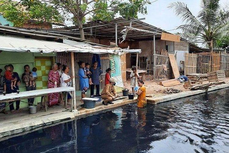 Pj Bupati Bekasi Dani Ramdan saat menghampiri warga yang sedang mandi di pinggir Kali Cilemahabang.