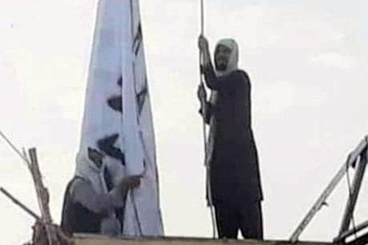Para militan kibarkan bendera Taliban di pos perbatasan Afghanistan-Pakistan. [Twitter Via BBC]