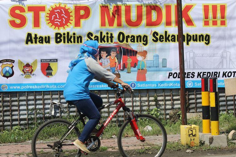 Warga melintas di depan spanduk bertuliskan stop mudik di Kota Kediri, Jawa Timur, Rabu (8/4/2020). Polresta Kediri mengimbau masyarakat untuk tidak mudik guna menghindari penyebaran COVID-19. ANTARA FOTO/Prasetia Fauzani/aww.