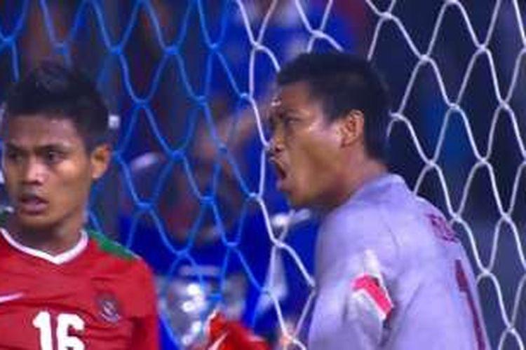 Kiper timnas Indonesia, Kurnia Meiga, menggagalkan penalti kapten Thailand, Teerasil Dangda, pada final Piala AFF 2016 di Stadion Rajamangala, Sabtu (17/12/2016).