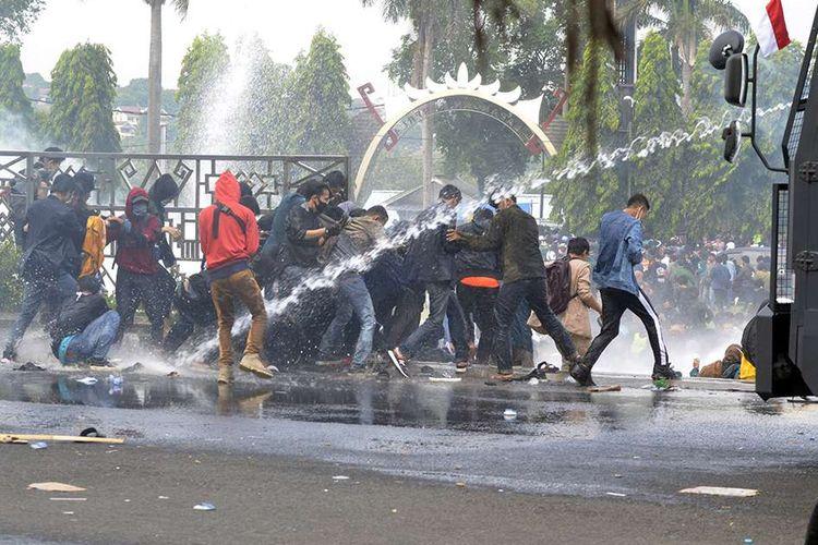 Sejumlah Mahasiswa berhamburan saat bentrok dengan pihak Kepolisian pada aksi demonstrasi di lingkungan kantor Pemerintah Provinsi Lampung, Lampung, Rabu (7/10/2020). Aksi tersebut sebagai penolakan RUU Cipta Kerja yang telah disahkan oleh DPR RI.
