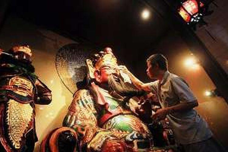 Petugas Kelenteng Darma Ramsi, Bandung, Jawa Barat, Rabu (3/2/2016), membersihkan patung Dewa Kwan Kong di altar untuk menyambut peribadatan tahun baru Imlek. Selain pusat pertokoan dan rumah warga, tempat ibadah kelenteng pun mulai bersiap menyambut perayaan tahun baru Imlek.