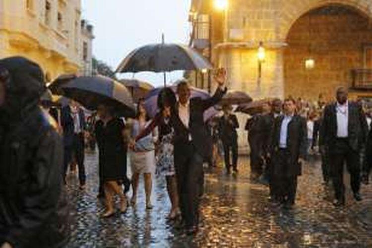 Presiden Barack Obama bersama istri menikmati Kota tua Havana di Kuba dengan berjalan kaki di bawah guyuran hujan.