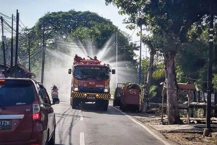 Penyemprotan cairan disinfektan di jalan raya oleh petugas damkar