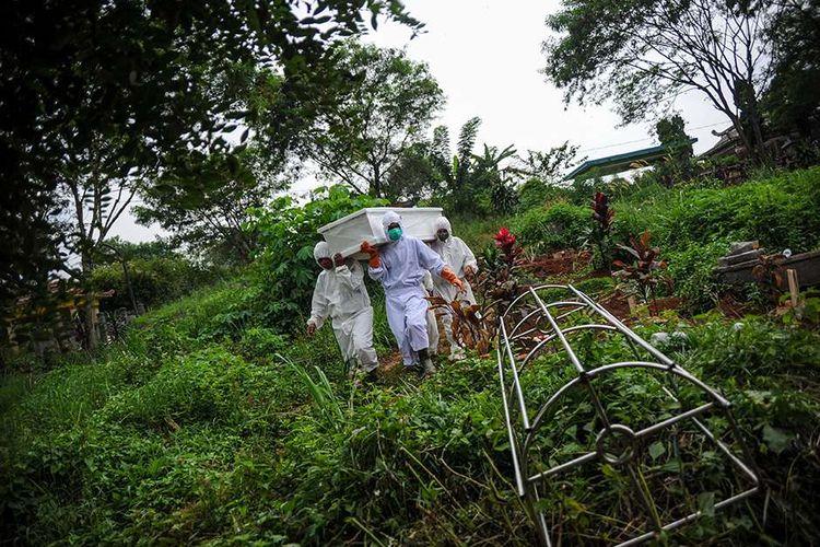 Tenaga pikul membawa jenazah dengan protokol COVID-19 untuk dimakamkan di TPU Cikadut, Bandung, Jawa Barat, Selasa (15/6/2021). Petugas pikul jenazah mengatakan, pemakaman jenazah dengan protokol COVID-19 di TPU Cikadut mengalami peningkatan sebanyak 20 hingga 30 jenazah per hari dibandingkan dengan bulan lalu yang hanya lima hingga delapan jenazah per hari.