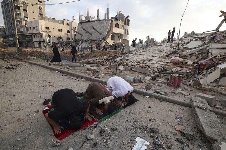 Muslim Palestina ketika melakukan Shalat Idul Fitri di luar bangunan yang hancur terkena serangan udara Israel di kawasan Beit Lahia, Gaza, pada 13 Mei 2021. Angkatan udara Israel menyatakan melakukan sejumlah serangan untuk menggempur Hamas, faksi Palestina yang menguasai Gaza.