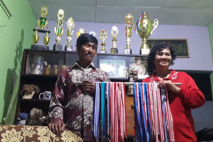 Budi Sutrisno dan Suliasih, orang tua Jafro Megawanto saat menunjukkan medali dan piala anaknya di rumahnya, Kelurahan Songgokerto, Kota Batu, Minggu (26/8/2018)