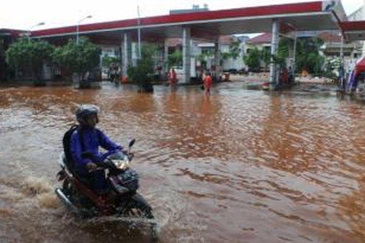 Banjir yang merendam kawasan Penjaringan, Jakarta Utara ikut melumpuhkan aktivitas bisnis setempat, Selasa (9/2/2015). Nampak jalan di depan salah satu SPBU di jalan itu, ikut kebanjiran.