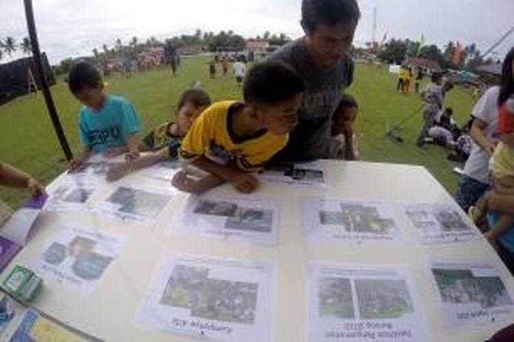 Warga melihat-lihat informasi mengenai upaya pelestarian Maleo dan Penyu yang dipajang pada Festival International Maleo dan Penyu Tompotika yang diselenggarakan oleh Aliansi Konservasi Tompotika di Kabupaten Banggai, Sulawesi Tengah.