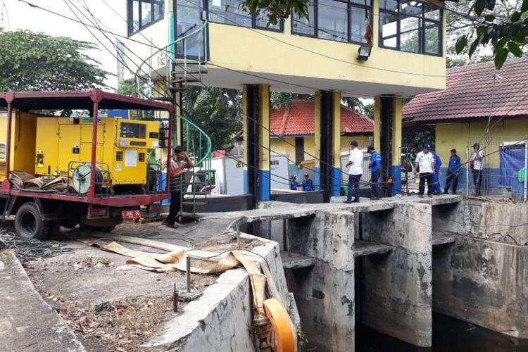 Sejumlah petugas tengah memasang pompa di Pintu Air Honda 1, Cempaka Mas, Jakarta Pusat, Rabu (25/7/2018).