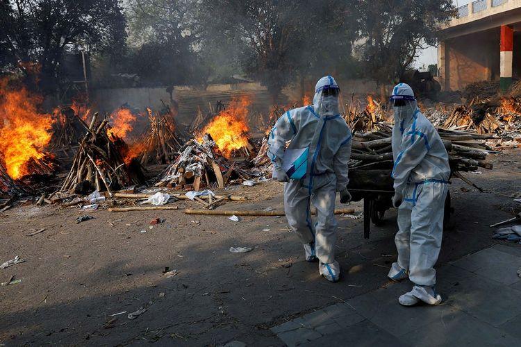 Petugas kesehatan yang mengenakan alat pelindung diri (APD) membawa kayu untuk menyiapkan tiang pemakaman untuk korban penyakit virus corona (COVID-19) selama kremasi massal di krematorium di New Delhi, India, Senin (26/4/2021).