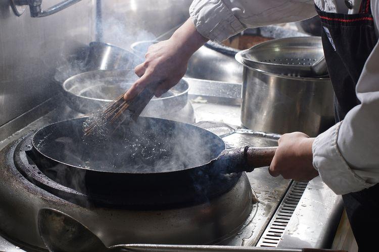 Ilustrasi seseorang sedang membersihkan wok.