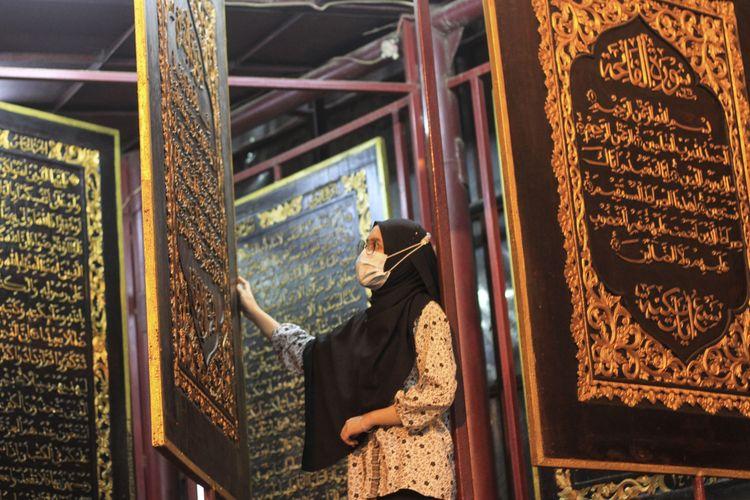 Seorang wisatawan lokal sedang berkunjung ke Al Quran Al-Akbar atau yang sering disebut Al Quran yang terletak di terletak di Jalan Mohammad Amin, Gandus, Kecamatan Gandus,Palembang, Sumatera Selatan, Sabtu (24/4/2021).