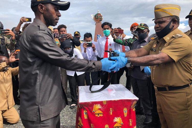 Anggota DPRD Puncak Jaya, Koti Weya menyerahkan senjata api milik mantan Anggota KKB Tendison Enumbi, kepada Bupati Puncak Jaya, Yuni Wonda, Papua, Senin (22/6/2020)