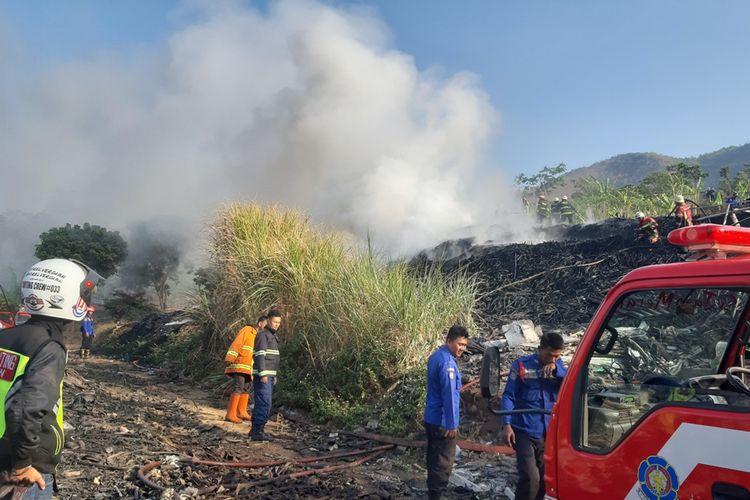 Petugas pemadam kebakaran berjibaku memadamkan api yang membakar tumpukkan limbah karet di wilayah Desa Mangunarga, Cimanggung, Sumedang, Jawa Barat, Sabtu (28/9/2019). AAM AMINULLAH/KOMPAS.com