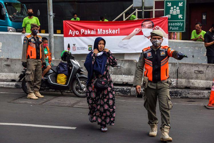 Petugas Satpol PP menggelar penggunaan masker dengan baik dan benar dalam Operasi Yustisi Protokol COVID-19 di Kawasan Tanah Abang di Jakarta Pusat, Senin (14/9/2020).  Operasi Yustisi tersebut dilaksanakan untuk menertibkan masyarakat agar lebih disiplin dalam menerapkan protokol kesehatan pencegahan penyebaran Covid-19.
