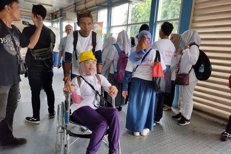 Siregar (40), tampak mendorong kursi roda Icha di halte TransJakarta Kota, Jakarta, Selasa (3/12/2019).