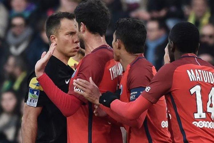 Wasit Johan Hamel (kiri) berbicara dengan gelandang Paris Saint-Germain Thiago Motta (dua dari kiri) terkait keputusannya mengganjar gelandang Marco Verratti dengan kartu kuning dalam pertandingan Ligue 1 melawan Nantes,  Sabtu (21/1/2017).
