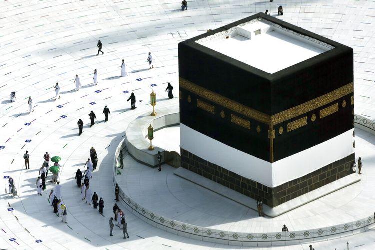 Para jemaah mengelilingi Ka'bah di Masjidil Haram, dengan mengenakan masker dan menjaga jarak sosial, pada Sabtu (17/7/2021).  Selama dua tahun berrturut-turut, ibadah haji dibatasi dengan ketat karena virus corona.