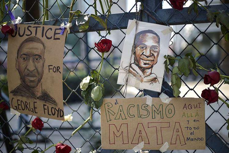 Potret George Floyd dan kertas bertuliskan Rasisme membunuh, di sini, di sana, dan di seluruh dunia, digantung sebagai bentuk protes di pagar kedutaan AS di Mexico City, Sabtu (30/5/2020). Kematian George Floyd setelah lehernya ditindih lutut polisi berkulit putih di Minneapolis, AS, turut menimbulkan reaksi keras dari banyak orang di berbagai negara.