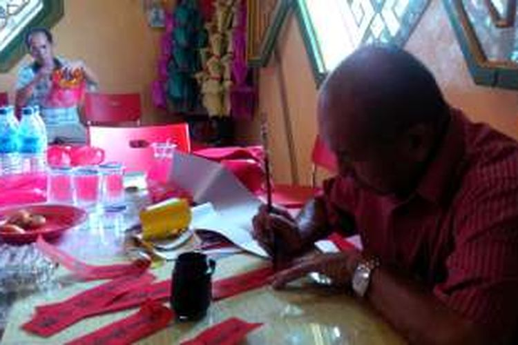 Gunawan (74) terlihat sedang menulis di atas secarik kertas berwarna merah di salah satu sudut ruangan Vihara Samudera di Pontianak, Kalimantan Barat, Rabu (3/2/2016).