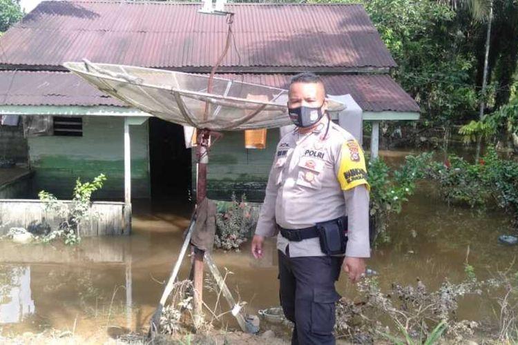 Petugas kepolisian mengecek kondisi banjir yang sudah berangsur surut di Kelurahan Pangkalan Kasai, Kecamatan Seberida, Kabupaten Inhu, Riau, Sabtu (14/11/2020).