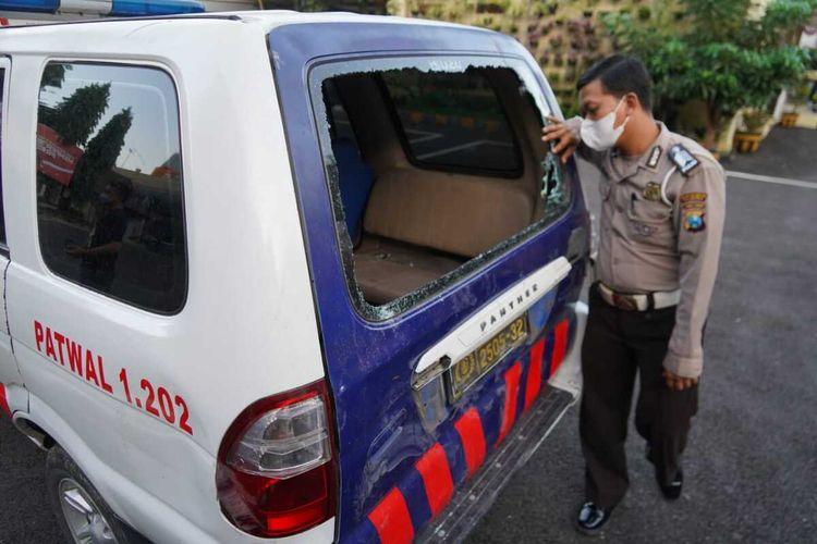 Mobil patroli polisi yang dirusak massa saat peristiwa kericuhan Patroli PPKM Darurat di Surabaya.
