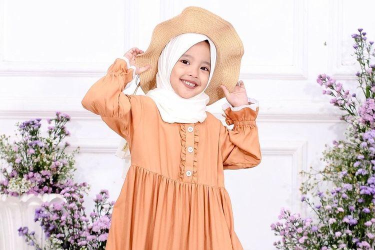Seorang anak berpose dengan hijab dan gamis dari Shahiahijab.
