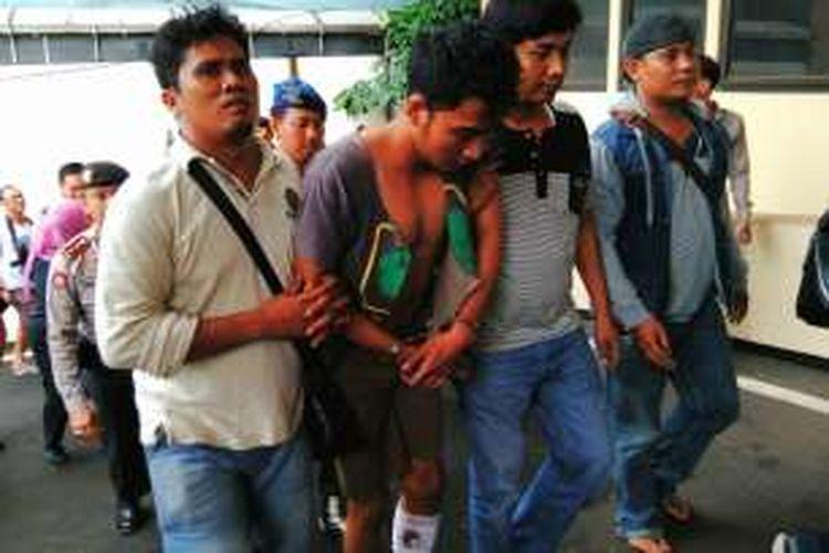 Aga Esanda (tengah foto) nampak berjalan dengan baju terbuka dan kaki bekas luka tembak. Aga merupakan salah satu pelaku pencurian serta pembunuhan terhadap Dedy Widyanarko di Cakung. Kamis (11/2/2016)
