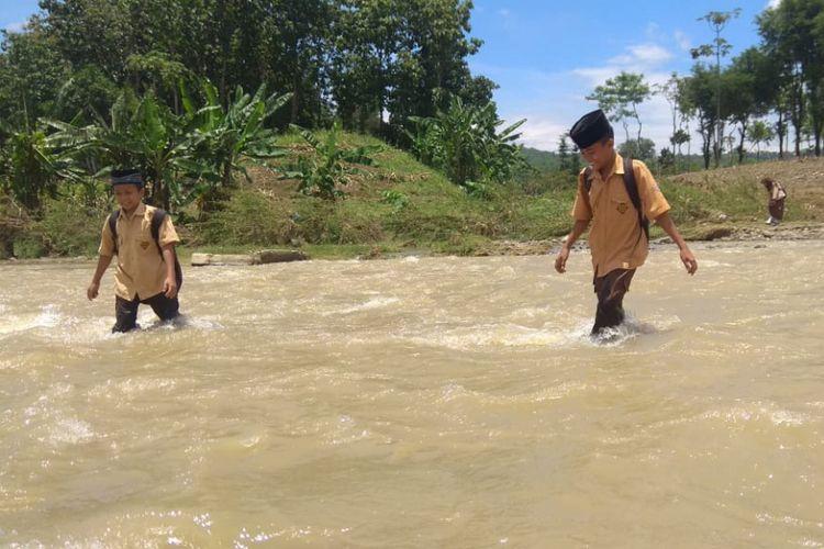 Siswa sekolah memberanikan diri menyeberang Sungai Belukar di Kendal karena jembatan yang biasa dilewati telah putus akibat arus deras pasca-hujan deras.