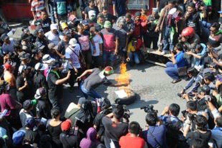 Sejumlah orang yang terdiri dari warga dan pekerja seks komersial (PSK) membakar surat undangan deklarasi penutupan kawasan prostitusi Dolly dan Jarak saat melakukan aksi, di Surabaya, Rabu (18/6/2014). Warga di kawasan prostitusi tersebut menolak menghadiri deklarasi penutupan yang rencananya akan digelar hari ini di Islamic Center, Jalan Dukuh Kupang, Surabaya.